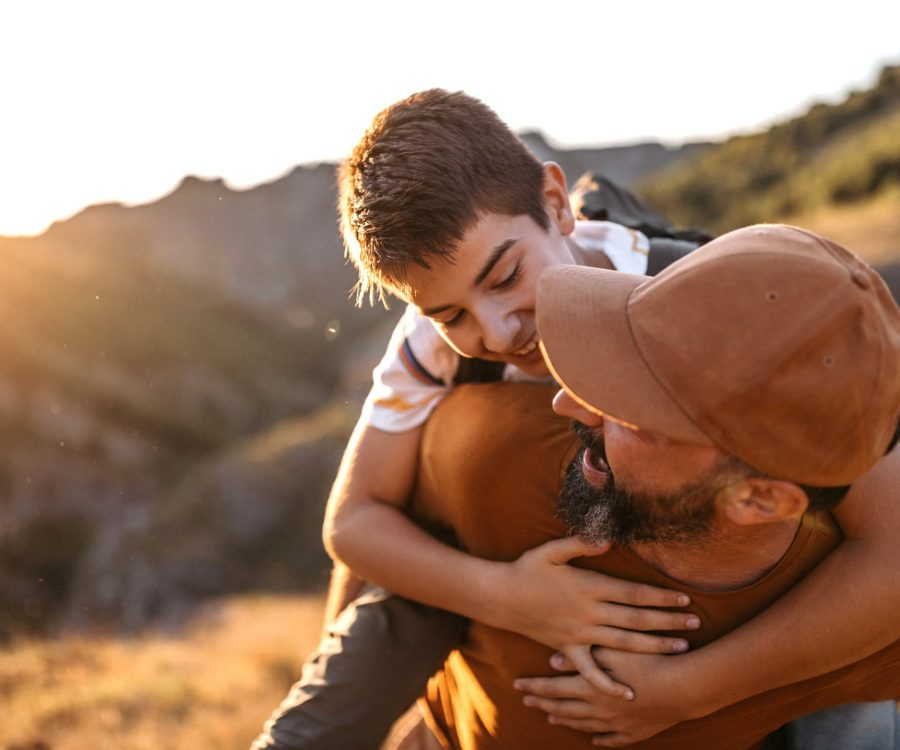 Cheerful dad carrying his teenage son on his back in nature on sunny summer day