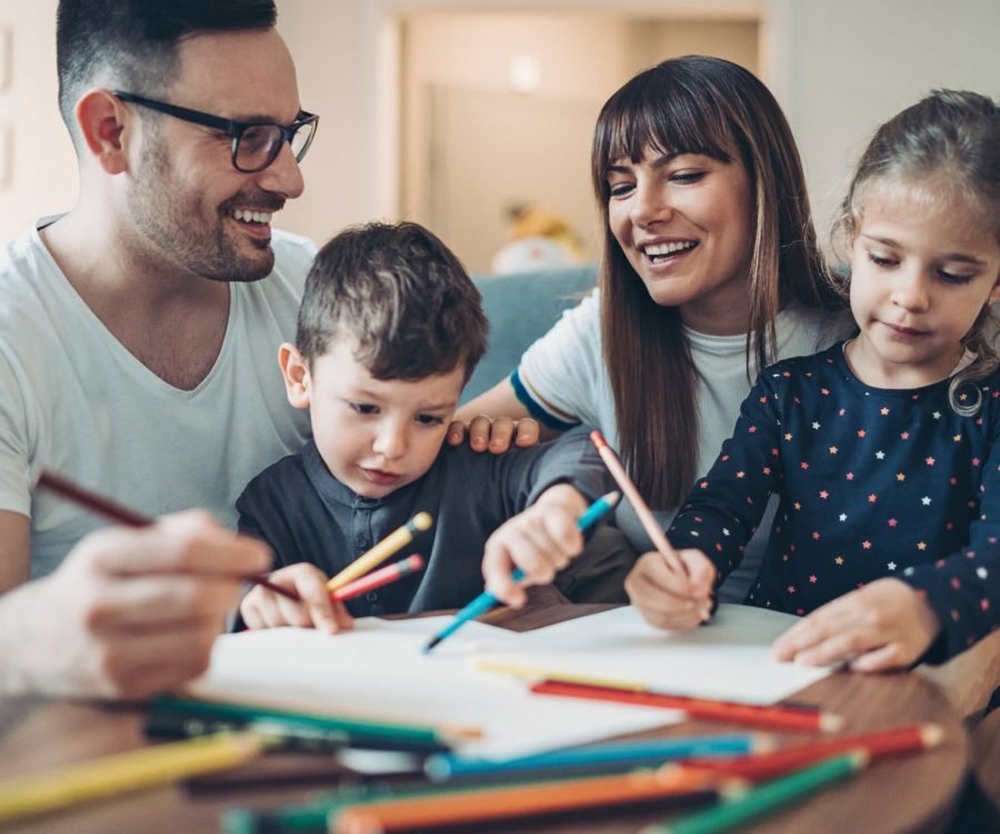 Two parents and a little boy drawing and writing together